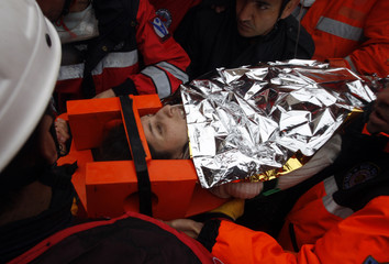 The surviving mother of a baby girl rescued from a collapsed building is taken to an ambulance in Ercis, near the eastern Turkish city of Van