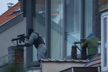 Belgium snipers secure the area from a rooftop near the scene where shots were fired during a police search of a house in the suburb of Forest near Brussels