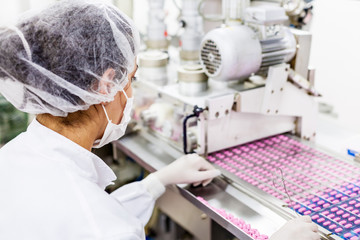 Woman working at the drugs factory, selection of the pink pills on the production line.Pharmaceutic industry