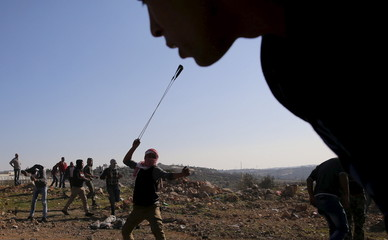 Palestinian protester uses a sling to hurl stones towards Israeli troops during clashes in the West Bank village of Silwad, near Ramallah