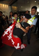 A policeman drops his hat while clashing with a protester during anti-Japanese protest in Hong Kong