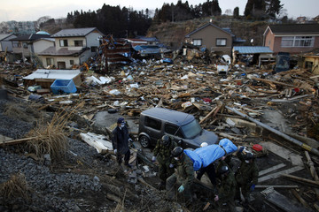 Members of Japan's Self-Defense Forces carry the body of a victim found in the ruins of Kesennuma, more than a week after the area was devastated by an earthquake and tsunami