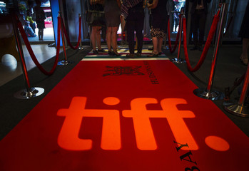 People stand on a red carpet behind the TIFF logo at the Toronto International Film Festival in Toronto