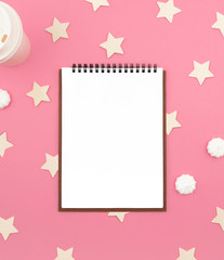 Notebook on a pink background, star and coffee, bird. View from above. Flat lay