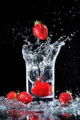 Glass of water and strawberries, splashing.