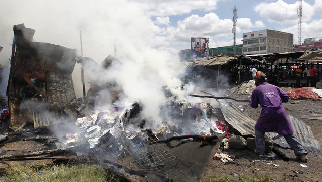 A trader tries to salvage his merchandise from a fire at the City Stadium open air market in Nairobi