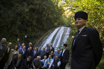 A delegation of diaspora Circassians pose for a family photograph at a waterfall in Bolshoy Kichmay, Greater Sochi