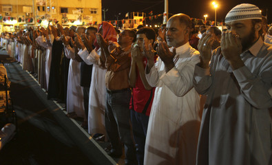 Libyan men perform the evening prayer during the holy month of Ramadan in the rebel stronghold of Benghazi