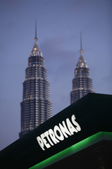 Malaysia's Petronas Twin Towers are pictured in the background as a Petronas logo is seen on the roof of its natural gas station in Kuala Lumpur