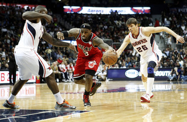 Heat forward James drives past Hawks Korver and Johnson in the first half of their NBA basketball game in Atlanta
