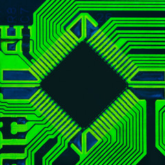 Abstract photo of an electrical board with a microprocessor in the center