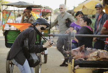 Tourist Ruangwattanasuk takes pictures of a traditional Cuban roast pig at a stall near the shrine of Saint Lazarus in Rincon