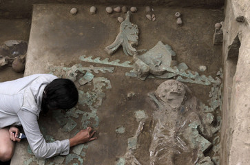 An archaeology student cleans the tomb of a priestess from the Moche culture in Trujillo
