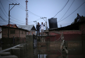 Flood victims call for help as they stand on the roof of their submerged house in flood waters in Srinagar