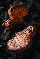 Two juicy freshly roasted steaks on the coals. Close up, selective focus