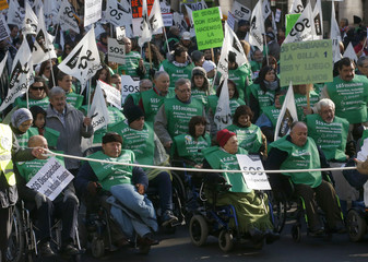 People in wheelchairs wave flags and carry signs during a rally against government cutbacks for disabled people in Madrid