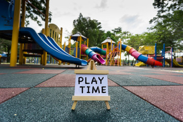 Conceptual image with word PLAY TIME on white canvas frame with wooden easel over blurred playground at background