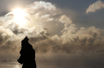 A man is silhouetted against the sun and arctic sea smoke rising off Lake Michigan in Chicago