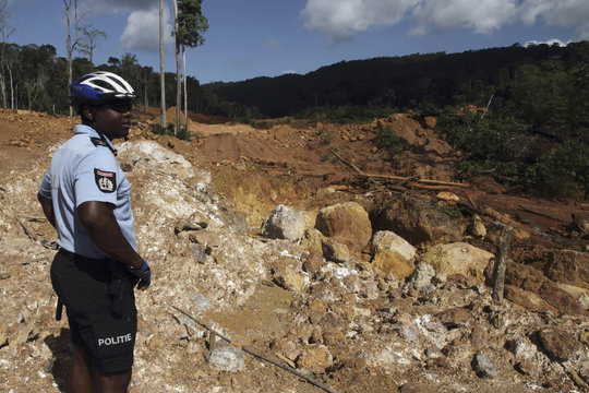 A Surinamese police officer observes the environmental damage left by wildcat gold miners in Brokopondo