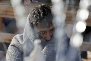 A migrant waits behind a border fence at the Greek-Macedonian border