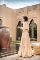 Pretty Arab woman in traditional  Moroccan dress standing in arabic spa and looking away. Ramadan holiday theme.