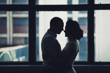 Happy couple hugging near window