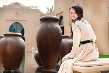 Traditional Arab woman in traditional  Moroccan dress sitting in arabic pool and looking in the camera  with the water on background. Ramadan holiday theme.
