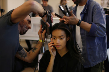 A model gets her hair done backstage before the Bill Gaytten Spring/Summer 2017 women's ready-to-wear collection for fashion house John Galliano during Fashion Week in Paris