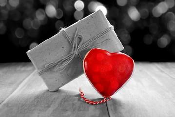 красивая фигурка красного сердце и подарок на черно белом фоне
