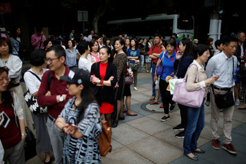 Parents wait for their children outside a high school during the first part of China's annual national college entrance exam, in Shanghai