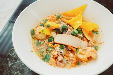 Thai-Style Spicy Tom Yum Noodle Soup in a White Bowl