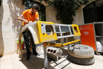 Jordanian graphic designer Abdelrahman Asfour, who turns car parts into furniture, works at his workshop in Amman