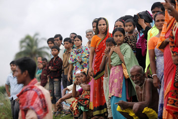 People wait for news of their missing relatives by the River Shitalakkhya, after a ferry was struck by a sand barge and capsized in Narayanganj