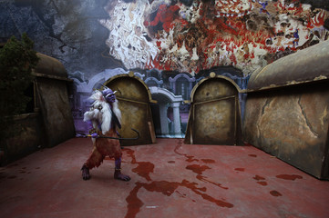 """An actor dressed as a ghost walks past a """"5D haunted house"""" at Hong Kong Ocean Park"""