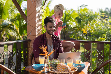 Couple Sitting On Summer Terrace Use Laptop Computer Having Breakfast Talking, Man And Woman In Morning Eating Outdoors With View On Tropical Forest