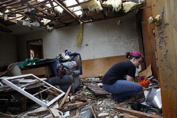 A woman looks through her destroyed home after a tornado hit Joplin