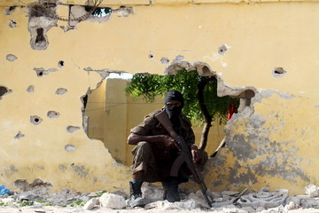 A Somali soldier takes position at the scene of a suicide attack by al Shabaab militants in capital Mogadishu