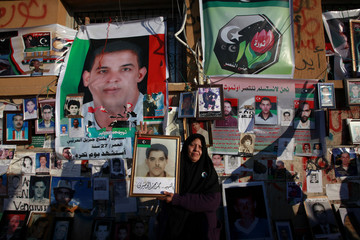 Fatma holds a picture of her son Hamad al Hathderi who was killed at Abuslin prison in Tripoli in 1996 as she stands in front of pictures of other people who died in the same prison during an anti-Gaddafi demonstration in Benghazi