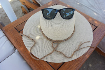 close up of hat and sunglasses at the beach