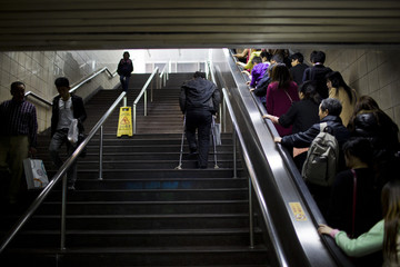 A man using crutches climbs a flight of stairs at a subway station in downtown Shanghai