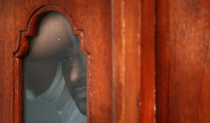 A member of defeated presidential candidate General Sarath Fonseka's security staff looks out a window in Colombo