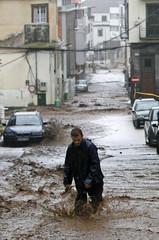 A man walks along a flooded street in downtown Funchal
