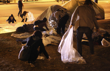 Protesters pick up trash from the Occupy Los Angeles encampment at City Hall Park after the deadline for eviction from City Hall Park passes in Los Angeles