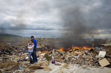 Michael Stanek hugs his daughter Kennedy Stanek as they take a break from helping friends sift though the rubble of their homes in Vilonia, Arkansas