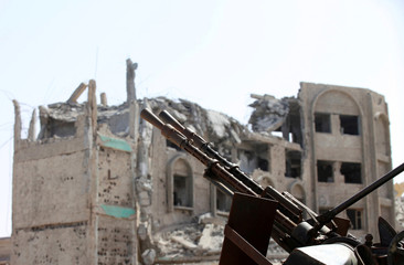 A weapon is seen in front of a building that was destroyed during a battle between Libyan forces allied with the U.N.-backed government and Islamic State militants in neighborhood Number Three, in Sirte