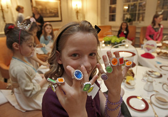 Vivienne Bartels, 7, shows off costume jewelry while taking tea during a 'Princess Prep' class training afternoon to learn how to be a princess in London