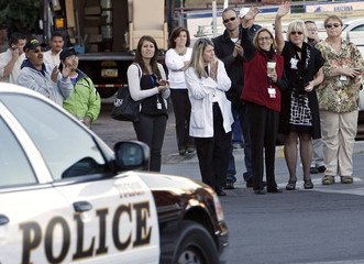 Workers wave as the medical ambulance transporting Gabrielle Giffords leaves the University Medical Center in Tucson