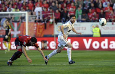 Osasuna's Miguel Flano fights for the ball with Real Madrid's Xabi Alonso during their Spanish first division soccer match at Reyno de Navarra stadium in Pamplona