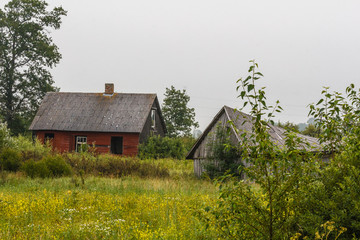 Abandon red house and gray barn in the country.