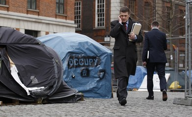 A pedestrian talks on the phone as he walks past tents in the Occupy London encampment outside St. Paul's Cathedral in London